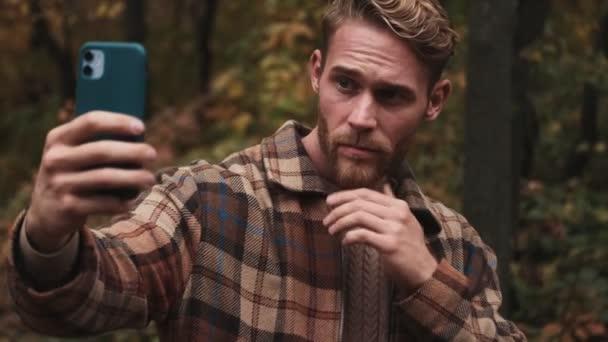 Ein zufriedener blonder Mann macht ein Selfie-Foto mit dem Handy beim Spaziergang im Herbstpark