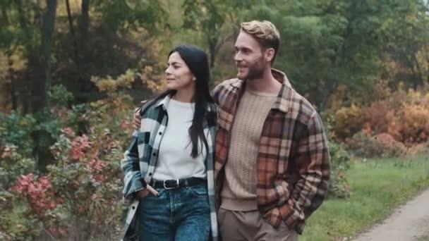 Egy boldog fiatal pár együtt sétál az őszi parkban.