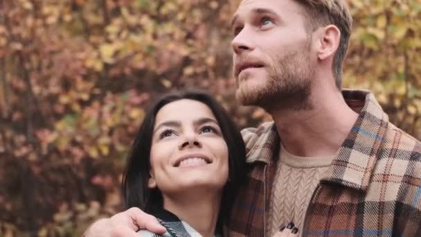 Egy fiatal szerelmespár ölelkezik az őszi parkban.