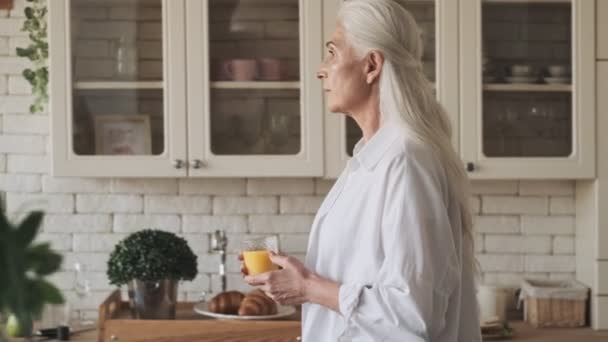 Pretty senior woman walking in kitchen with juice indoors at home