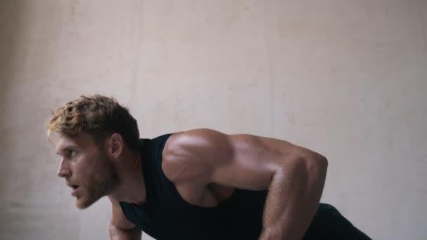 Svalnatý blondýnka muž dělá tlačí nahoru cvičení v šedém studiu