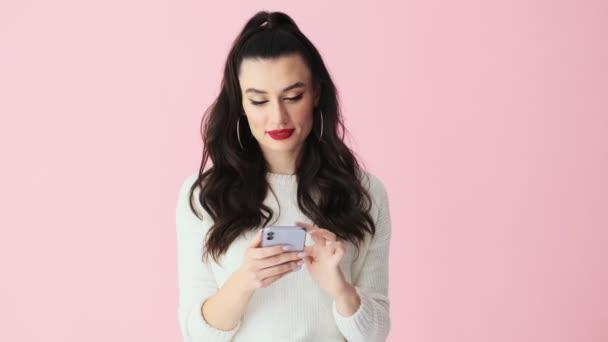 Eine glückliche Frau mit roten Lippen macht Siegergeste, während sie mit ihrem Smartphone isoliert vor rosa Hintergrund im Studio steht