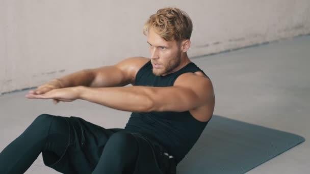 Vážný muž dělá cvičení ležící na podložce jógy a pumpuje svůj lis v šedém studiu