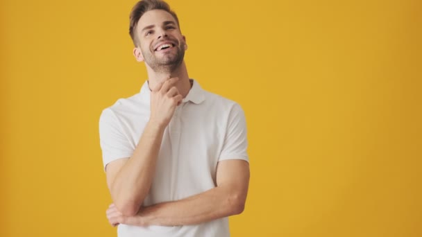 Handsome young positive thinking man isolated over yellow wall background