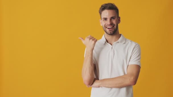 Handsome young happy positive man showing copyspace isolated over yellow wall background