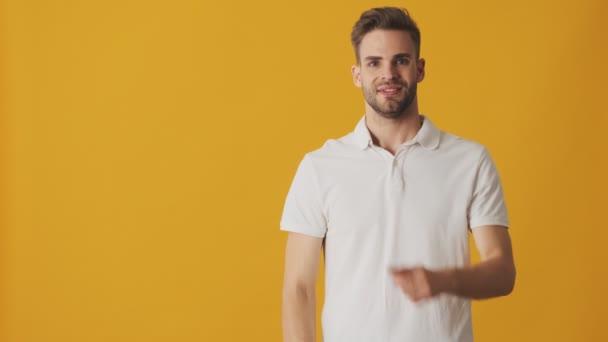 Fešák mladý šťastný pozitivní muž ukazující copyspace izolované přes žlutou zeď pozadí