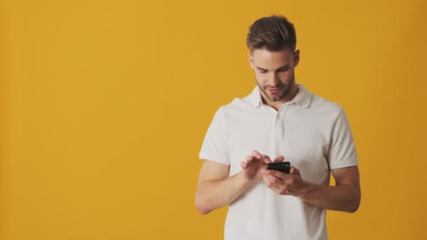 Handsome young cheerful man using mobile phone isolated over yellow wall background