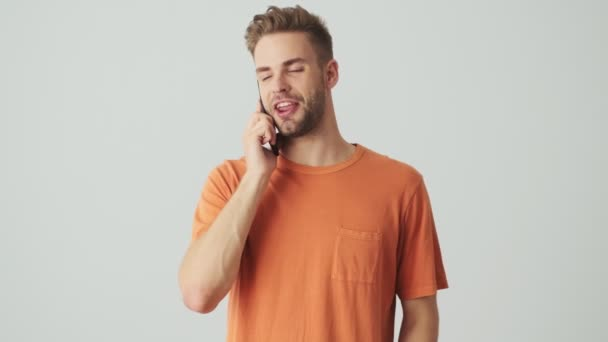 Handsome young cheerful man talking by mobile phone isolated over grey wall background