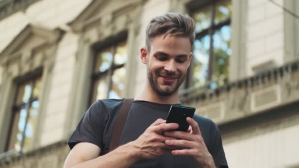 Young optimistic man using mobile phone outdoors on the street