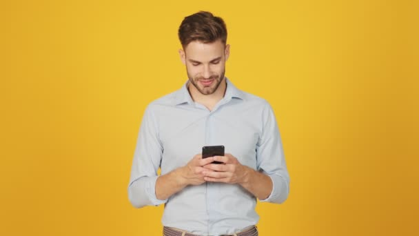 Soustředěný mladý muž používá svůj chytrý telefon, který stojí izolovaný nad žlutým pozadím ve studiu