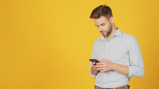 An attractive young man is using his smartphone standing near free space isolated over a yellow background in the studio