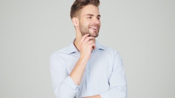 Ein lächelnder junger Geschäftsmann posiert isoliert vor grauem Hintergrund im Studio vor der Kamera