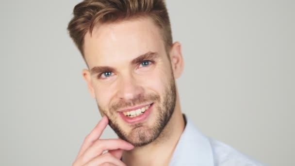 Eine Nahaufnahme zeigt einen gut aussehenden jungen Geschäftsmann, der isoliert vor grauem Hintergrund im Studio vor der Kamera posiert.