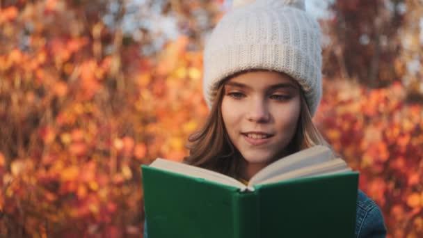 Ein lächelndes junges blondes Mädchen liest draußen im Park
