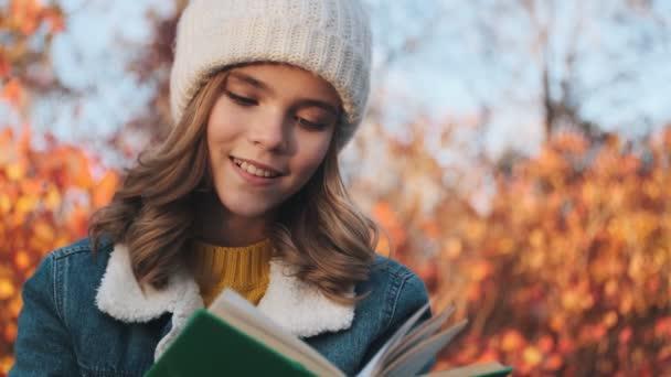 Pozitivní mladá blondýnka čte venku v parku