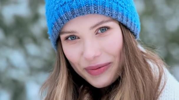Eine Nahaufnahme zeigt eine schöne junge Frau mit blauem Winterhut, die im Winter draußen im Central Park vor der Kamera posiert.