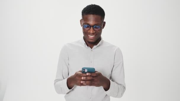Usmívající se africký Američan nosí brýle je pomocí svého smartphonu stojící izolované nad bílým pozadím ve studiu
