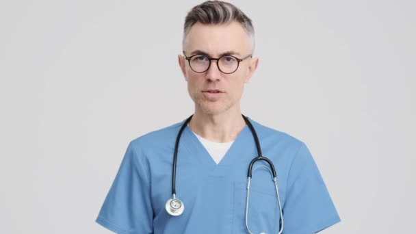 A displeased senior doctor man wearing medical uniform is shaking his hand negatively standing isolated over grey background in the studio