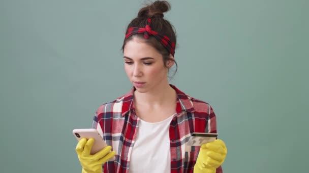 Eine zufriedene Putzfrau bedient ihr Smartphone, während sie eine Kreditkarte in der Hand hält, die isoliert über einem grünen Hintergrund im Studio steht