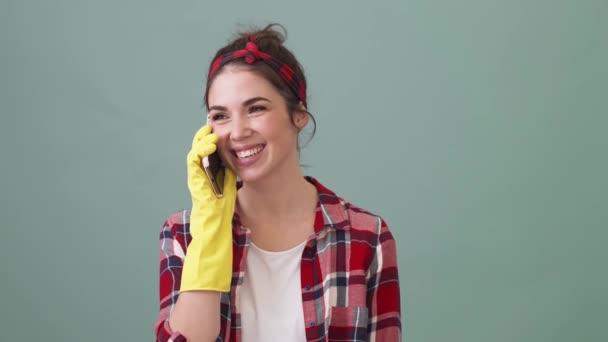 Eine zufriedene Putzfrau spricht auf ihrem Smartphone, das isoliert über einem grünen Hintergrund im Studio steht.