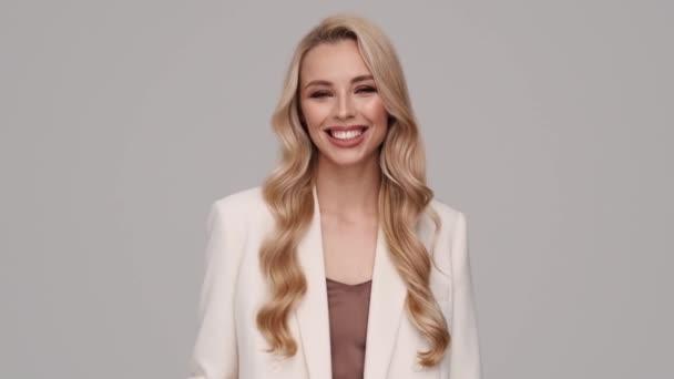 Krásná mladá blondýnka podnikatelka pózuje na kameru, zatímco stojí izolované přes šedé pozadí ve studiu