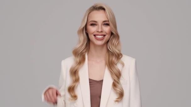 Egy mosolygó szőke üzletasszony köszönt a kamerának, miközben szürke háttérrel áll elszigetelve a stúdióban.