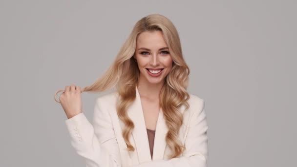 Jistá mladá blondýnka podnikatelka mrká na kameru stojící izolovaně nad šedým pozadím ve studiu