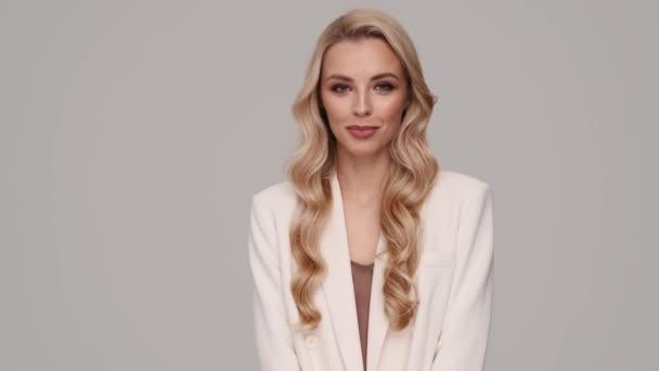 Usmívající se mladá blondýnka podnikatelka se dívá na kameru stojící izolovaně nad šedým pozadím ve studiu