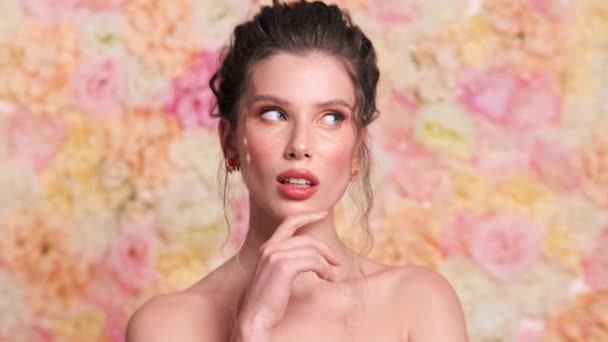 Potěšená mladá žena přemýšlí o něčem, co stojí izolovaně nad květinovým pozadím ve studiu