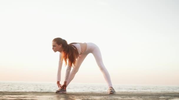 Mladá ryšavá žena sportovkyně v bílém sportovním obleku se ráno protahuje venku u moře