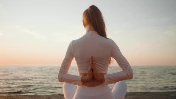 Eine junge rothaarige Sportlerin in weißem Sportanzug sitzt morgens in einer Yoga-Pose draußen am Meer.