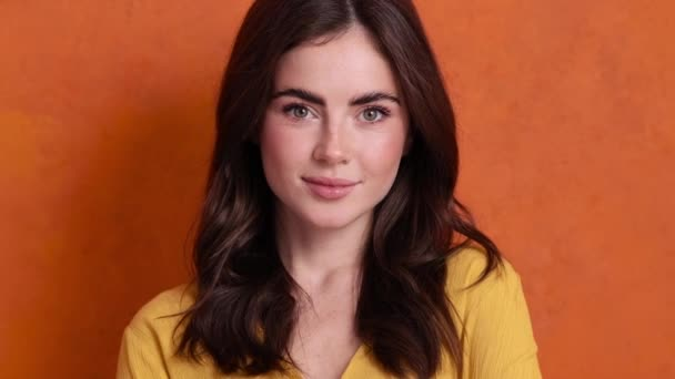 Okouzlující mladá žena se dívá na kameru stojící izolované nad oranžovým pozadím ve studiu