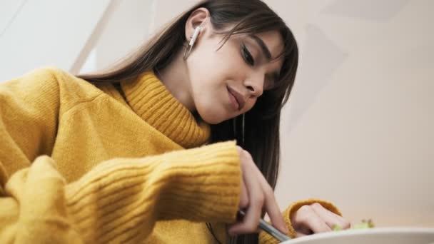 Detailní záběr ženy ve sluchátkách a žlutého svetru, jak krájí jídlo na talíři nožem a vidličkou.