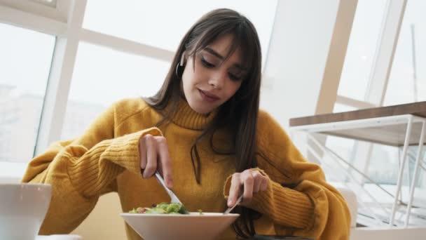 Ženy ve sluchátkách a žlutém svetru krájejí jídlo na talíři nožem a vidličkou a užívají si to v kavárně