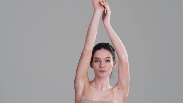 Něžná polonahá žena pózuje před kamerou, zatímco zvedá ruce nad šedou stěnu ve studiu. Snášenlivost rozmanitosti. Každé tělo je krásné.