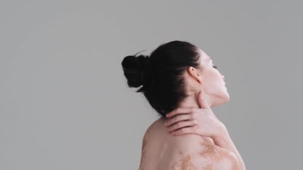 Zadní pohled na krásnou polonahou ženu stojí izolovaně nad šedou zdí ve studiu. Snášenlivost rozmanitosti. Každé tělo je krásné.