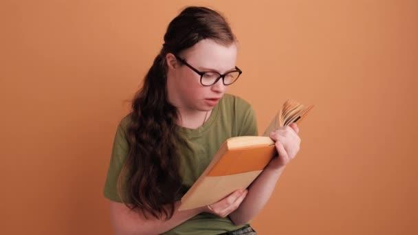 Egy fókuszált, Down-kóros fiatal lány ül és egy narancssárga fal felett elszigetelt könyvet olvas a stúdióban.