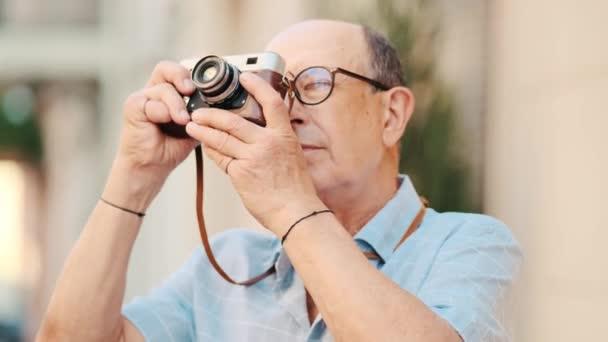 Ein älterer Mann mit Brille fotografiert aus nächster Nähe mit seiner Kamera, während er draußen auf der Straße spaziert