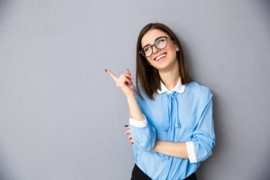 Cheerful businesswoman in glasses pointing away