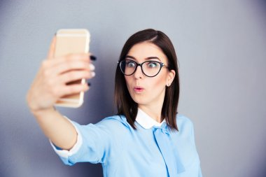 Surprised businesswoman making selfie photo on smartphone. Wearing in blue shirt and glasses. Standing over gray background stock vector