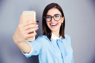 Laughing businesswoman making selfie photo on smartphone. Wearing in blue shirt and glasses. Standing over gray background stock vector