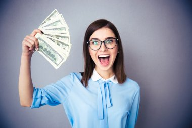 Laughing businesswoman holding bills of dollar