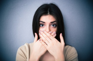 Portrait of a young woman covering her mouth