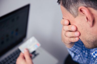 Upset man holding credit card