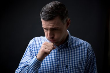 Portrait of a man coughing