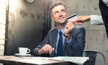 Man giving bank card to waiter