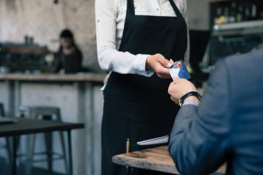 Man giving credit card to waiter in cafe