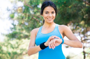 Smiling sporty woman using smart watch outdoors