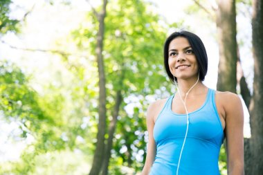 Smiling sports woman in headphones outdoors