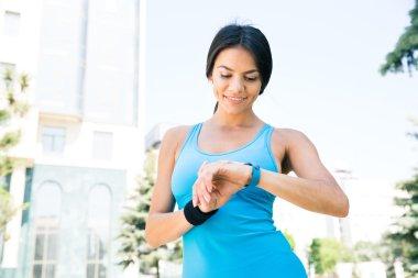 Happy sporty woman using smart watch
